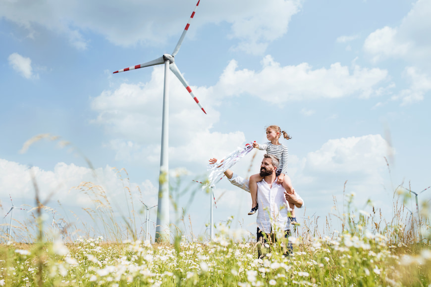 Father and daughter walking through a field with a wind turbine in the background