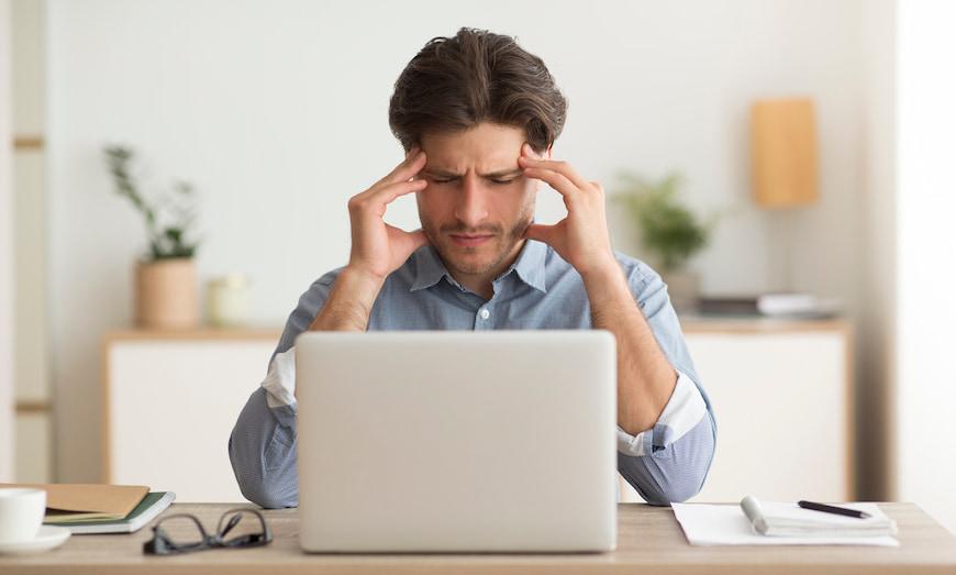 Man with an headache at his computer