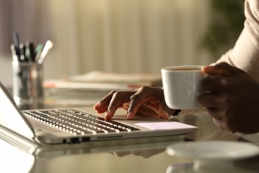 Man using computer while holding a cup of coffee.