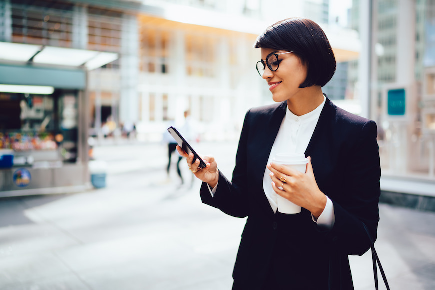 Female business-person checking their phone while holding a travel coffee cup.