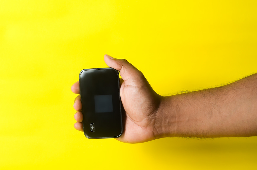 Man's hand holding a MiFi router in front of a yellow background