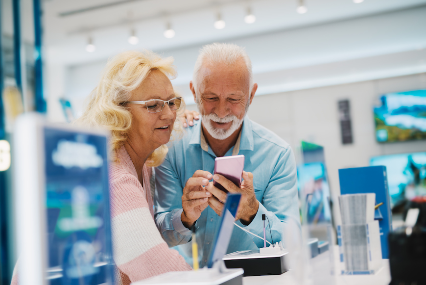 Elderly couple shopping for a new phone at a tech store.