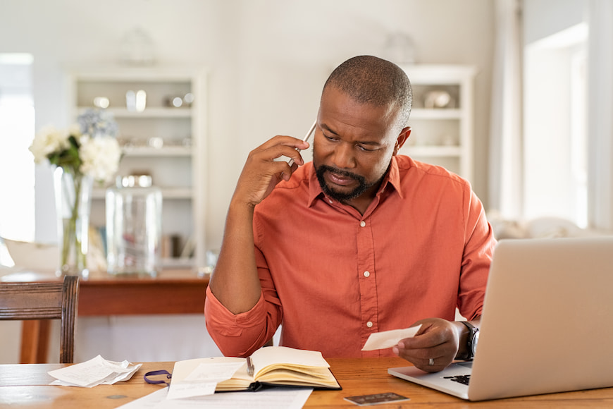 Man on the phone while using his laptop to pay bills