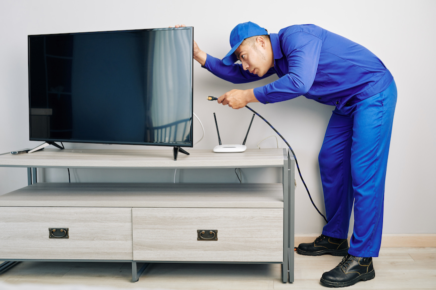 A man installing a new tv cable into a new TV.