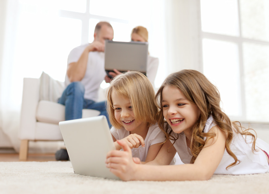 Two children play on a tablet together on a rub while their parents are on a computer in the background