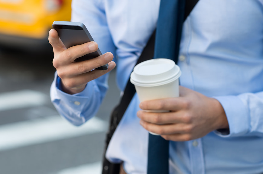 Man walking down the streeting using his phone while holding a coffee