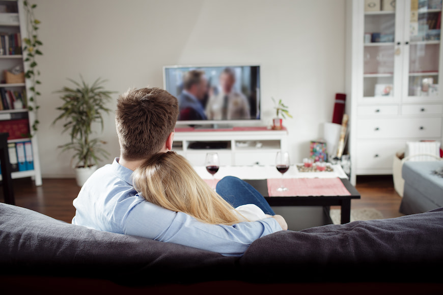 Couple watching tv together while sitting on the couch
