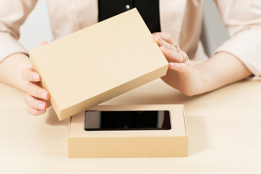 Person opens the box of a brand new mobile phone