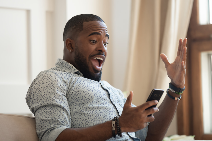 Man holding his phone looking very surprised